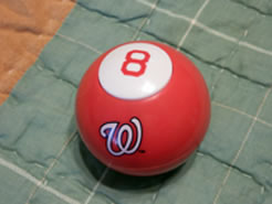 A red 8 ball, with curly white W logo on the side