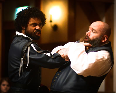 Othello in black leather grabs Iago by the throat