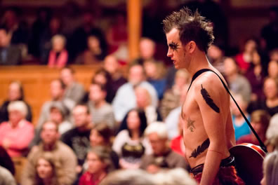 Ariel stands topless with feather tatoos on his arm and waist, starburst makeup arond his eyes, spiked hair, and a banjo draped over his should, with the Blackfriars Playhouse audience in the background.