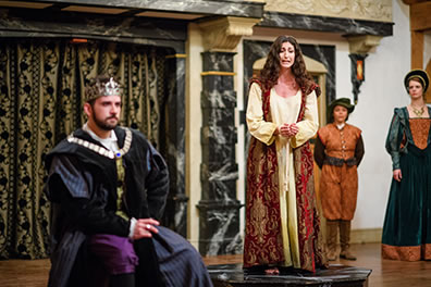 Production photo by Marek K. Photography of Hermione on a black marble like platform looking at Leontes, back to her, while the court watches in the background.