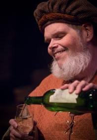 Production pic of Falstaff pouring a glass of wine