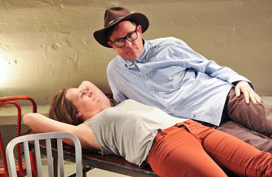 Orsino and Viola lie on table, Orsino in orange jeans and gray tanktop tee, Viola in blue striped work shirt, brown jeans, and wearing a brown cowboy hat and black framed glasses