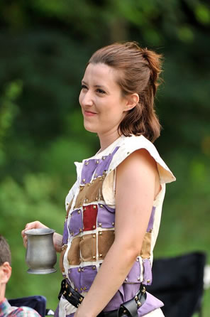Hal in a vest with purple, gold, and red patches intended to look like chain mail with a black sword belt around her waist holds a pewter mug in her hand. Trees are in the background.