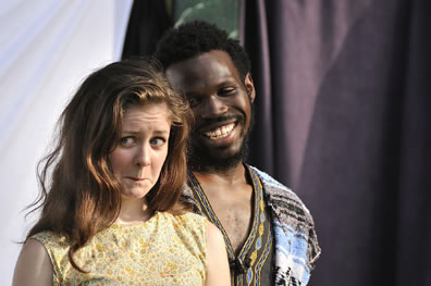 Phoebe with windswept brunette hair and wearing a yellow dress has a frown in her expression while behind her, Sylvius with Bohemian shirt and serape vest smiles broadly at her.