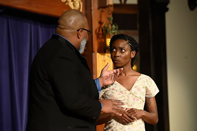 Production photo of Polonius talking with Ophelia, she looking up into his face with a sour but obedient expression.
