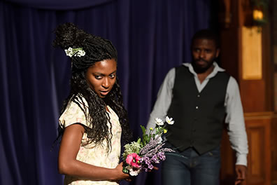 Production photo of Ophelia with flowers, looking away with a sly expression. Laertes is in the background.