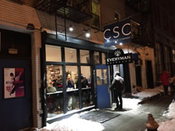 CSC marque over a glass-fronted section of building, a man opening the blue front door with lobby full of people inside the windows, snow on the edges of the sidewalk, and poster of Twelfth Night to the left of the windows. At night
