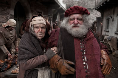 Mistress Quickly covered in raged clock holds onto Falstaff's Arm, who is in a medeivel lords jacket and cap with white beard and leather gloves in an narrow street with commercial activity in front of the houses