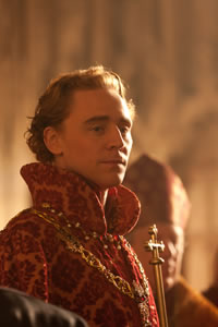 Henry V in regal cloak of red and gold, with a necklace around his neck and a bishop in the background