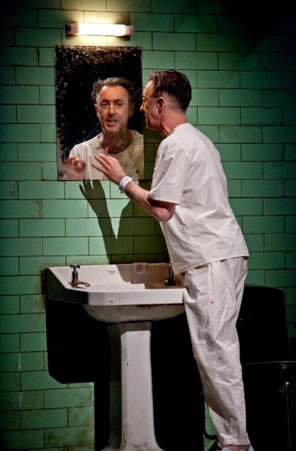 Alan Cumming at a sink and wearing hospital patient shirt and pants looks into the mirror