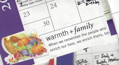 "A scattering of pocket calendars, opened to various months, featuring scribbled entries, and a message at the bottom of one page: ""Warmth + Family. When we remember the poeple who enrich our lives, we enrich theirs, too."""