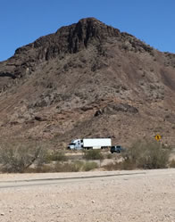 Photo of a rock-clif mountain surrounded by desert, with trucks passing on the highway at its foot