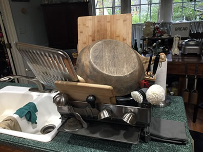 Photo of dish drainer filled with wood cutting boards and bowl, little silver bowls hanging off the side, and a broiler pan dangling off the edge over the sink.