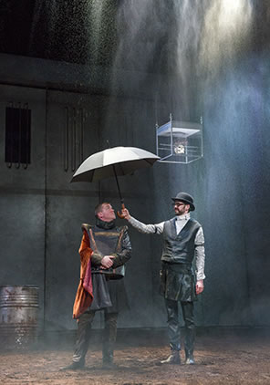 Production photo of Catesby and Hastings standing in the rain, Catesby, wearing a black bowler hat, black vest and white clerk's shirt, holding an umbrella over Hastings, who's in Elizabethan jerkin and skirt with a red cape on his shoulder.
