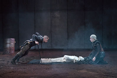 Production photo of Richard, leaning on his crutches over the white-shrouded corpse lying on the train of Anne's dress She is kneeling at the corpses' head, opposite Richard.