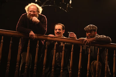Toby, with elbow on balcony railing, Aguecheek holding a flask and croutched behind the balcony railing, and Fabian with checkered dog cap next to him.