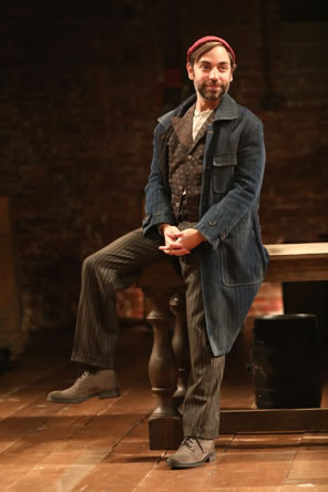 Feste in dirty blue overcoat, brown striped pants, brown dotted vest, and red knit cap sits on the edge of a large wooden table.