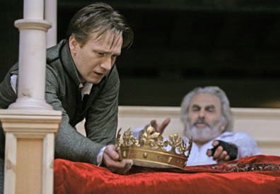 Hal holds the crown at the foot of the bed in which King Henry lies