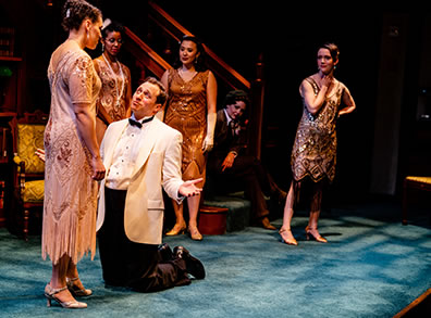 Production photo of Berowne, in white dinner, black bowtie and pants, kneeling before Rosaline.