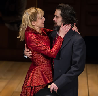 "Kate in a lovely red dress lovingly clasps Petruchio after he asks her to ""Kiss me Kate."""