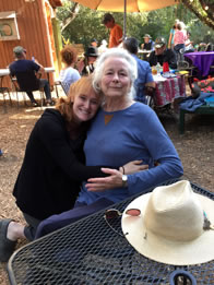 Photo of Willow Geer leaning on Ellen Geer's shoulder sitting at an outdoor table