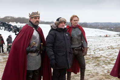 Irons and Hiddleston, dressed in medieval armor with red cloaks, stand on either side of Eyre in a parka and winter hat with snow on the ground and a camera boom in the background
