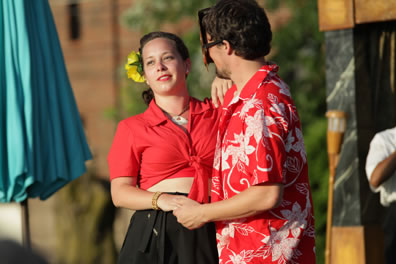 Beatrice in red shirt tied up to reveal a bare tummy above a black dress, a yellow flower in her hair, holds hands and has her other hand on the shoulder of Benedick as the dance, he in a red and white floral pattern shirt and wearing a mask. A big, blue beach umbrella is to the left.