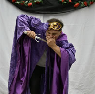 Production picture of Heirenomo in stage costume with daggar to mouth covered by other hand