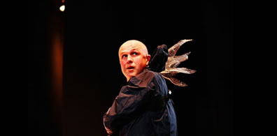 A man, bald, with a rain slickeer and fairy wings coming from the base of the hood