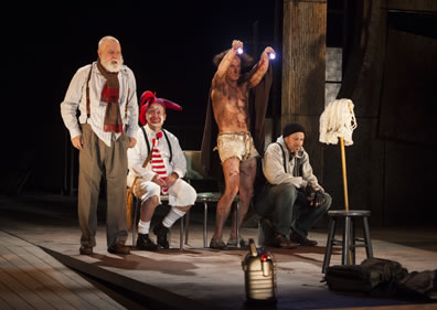 Lear stands in white untucked shirt, brown pants, suspenders, and red and brown scarf about his kneck, fool in white knee pants, socks, shirt, black suspenders, red-striped tie, red nose and white face with coxcomb sits, Edgar as Poor Tom with blanked around him and only in white cutoffs stands holding  up two flashlights, and Kent in black stocking  cap, gray hoody, fingerless gloves, and blue jean sits, all ecept the Fool looking at a mob stuck into a joint stool; Fool is looking up at Lear.