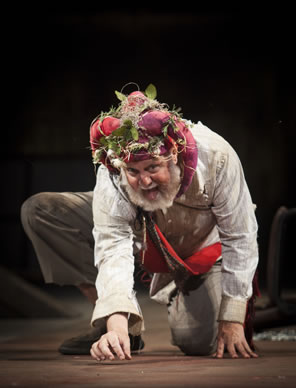 Lear, one knee on the ground, picking at the flor with his right fingers, wearing dirty white shirt and pants, his red regal sash, and the Fool's coxcomb covered in brambles