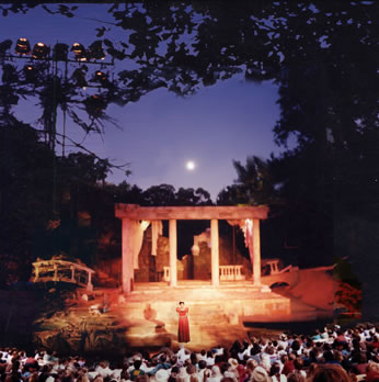 An audience watches a play on an outdoor stage under a moonlit sky