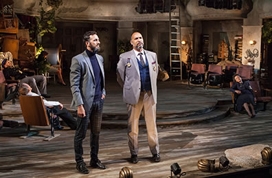 Production photo of Sebastian and ANtonio talking while the rest of the King's party sleeps in theater chairs.