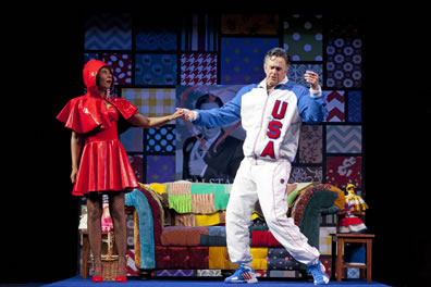Falstaff in a USA track suit dances with Alice Ford wearing a vinyl Red Riding Hood outfit in a quilt-laden living room