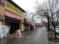 "Business district street, rain soaked sidewalk, and matress store to front left, with ""Big Sale"" board in front and matress leaning against wall"