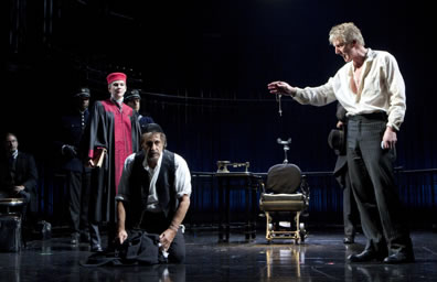 Production shot of trial scece: Antonio lroding over a kneeling Shylock with Portia looking on