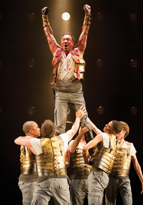Coriolanus, arms upraised, bload on his gold armor and uniform, is lifted high above by the other soldiers.