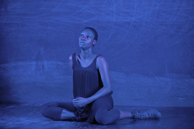 The black woman sits on the stage, wereing dark pleated tank dress over shin-length tights, her head tilted up and a tear running down her cheek