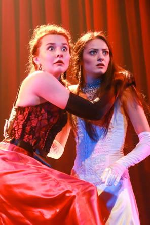 Helena in red dress and long black gloves and Hermia in white dress, long white gloves and jeweled necklace clasp each other with alarmed expressions.