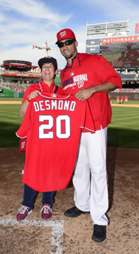Sarah standing next to Ian Desmond holding his jersey at home plate of Nationals Park