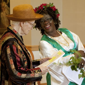 Old woman in multi-colored and black striped jacket, orange straw hat with script in hand next to a black woman with white blouse, bright green vest, and flowers in her hair