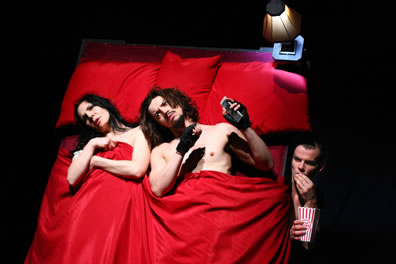 Kate and Petruchio in a bed with red sheets watching porn TV as Grumio, eating popcorn,  peers out from under the bed
