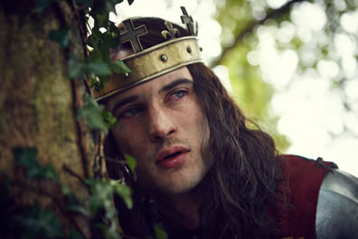 Henry VI, with a cross-topped gold headband as a crown, long hair, burgundy cloak over his armor, and bloodshot eyes, leans against an ivy-find tree trunck.