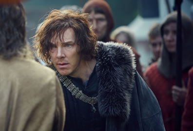 Richard in shaggy hair, a chain pendant draped over his blue shirt, and a fur-line cloak hunches over as he stairs at somebody with an army behind him.