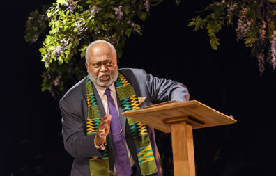 Preacher in gray suit, purple tie and an African scarf oer his shoulders stands at a podum with blooming tree branches overhead.